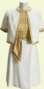 White linen and printed silk day dress worn by Queen Elizabeth II, designed by Ian Thomas, English, 1977. During the Silver Jubilee tour in 1977 The Queen and The Duke of Edinburgh spent three weeks in Australia visiting each state. On a visit to Melbourne Zoo, The Queen wore this dress and jacket designed by Ian Thomas. The dress has a bodice of caramel-coloured silk with a white geometric design, while the skirt is of white linen to match the short-sleeved jacket, which is trimmed in the…