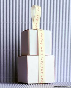 Martha Stewart - Poetic Stack - paper ribbon printed with a poem binds a stack of boxes.