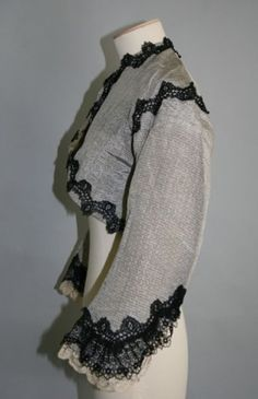 """Ca.1865 grey-blue striped shot silk fitted jacket, lined with cream glazed cotton. """"Silk edge facings: silk CF, sh, low edge."""" (Does this only refer to the lace trim, or does it also have silk facings inside?) Part of an incomplete woman's dress. Chertsey (England) Museum."""