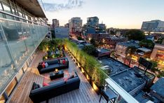 Our project Rooftop Vista. This terrace has a hot tub with a frosted glass privacy screen, a lounge area, dining area, as well as a small 3 seat bar that overlooks the bustling city of Toronto. The lighted pathway can also change colour, adding to the city view.