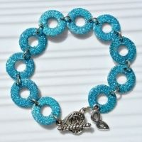 A bracelet made of metal washers coated in blue glitter. DIY for teens.