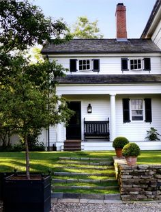 CURB APPEAL – another great example of beautiful design. white house with porch, black shutters + door.