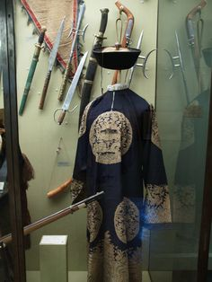 French Army Museum - Paris: Hat and robe of a Mandarin Chinese officer taken at the Battle of Chang-Kai_Wouan on September 18,1860. Surrounding the uniform are Boxer edged weapons.