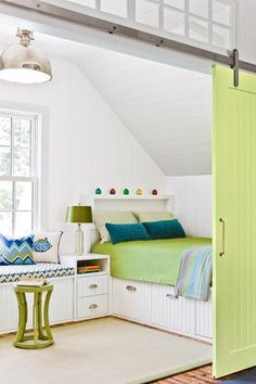 Sliding barn doors with stainless-steel hardware add definition and a touch of whimsy to this bedroom. Transom windows above the doors allow light to flow from one end of the third-floor space to the other. | Photo: Michael J. Lee | thisoldhouse.com