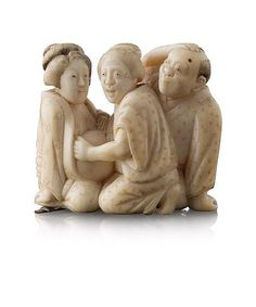 JAPANESE IVORY NETSUKE OF A PREGNANT WOMAN MEIJI PERIOD the seated woman attended by a midwife while an overwhelmed man looks on, signed 5cm high