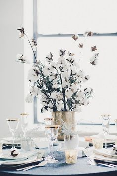 Table scape with a restrained palette of blue and white and layers of metallics and mercury glass