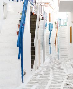 Mykonos, Greece, stone road, white walls, blue railing / Garance Doré