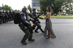 The image of a seemingly serene female protester making her stand has gone viral. This photo is destined to become iconic.