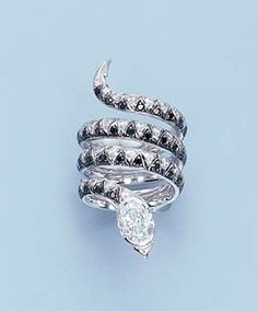 A DIAMOND AND BLACK DIAMOND SERPENT RING   Designed with a coiled body of white and black diamond scales to the oval-cut diamond head weighing 1.20 carats, ring size 4  With report no. 10836486 dated 27 September 1999 from the Gemological Institute of America stating that the diamond is D colour, internally flawless clarity