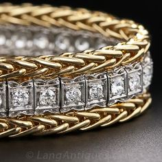 This platinum straightline diamond bracelet from the 1920s was updated in the 1940s, when yellow gold came back into fashion, with a 14 karat yellow gold wheat motif articulated border. In the glamorous 1940s jewelry had to be big and bold to be in style and this bracelet makes a solid statement with a beautiful flash of high-color European-cut diamonds.