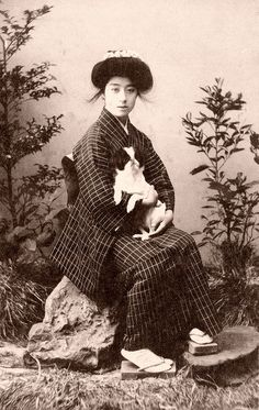 Geiko with a Chin Dog 1907    The Japanese Chin originated in China and was brought over to Japan around 732 CE. A favourite among 18th Century Courtesans they were called 'sleeve-dogs' or Chien de la Cour in French, as they were carried in the large sleeves of Japanese ladies.
