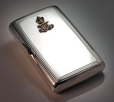 A rare World War I Russian Imperial presentation cigarette case with a jeweled gold cipher of Grand Duchess Maria Pavlovna the Elder.  The case was made at the workshop of Faberge's master goldsmith Gabriel Niukkanen. The gold Russian Imperial crown embellished with two cabochon cut sapphires and rose diamonds.  The gold thumbpiece is also embellished with a cabochon sapphire.