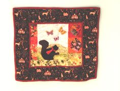 """Wall Hanging - 11. The Elusive Little Black Squirrel at Kolomoki made by Judith Lawrance. From Judith: """"While camping at Kolomoki Indian Mounds in Blakely, Georgia, we saw an unusual black squirrel scampering across a field with some ordinary gray buddies!  Every time we return to this site, we search in vain for that little fellow!  Alas, he seems to have disappeared! This quilt is an altered form of one block of a pattern by Bunny Hill."""""""