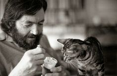 Julio Cortazar feeding his tabby cat