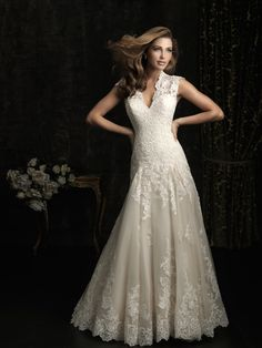 Style: 8965    This fitted A-line gown in all-over lace features a beautiful neckline with contoured straps that continue to a keyhole back. A chapel length train and covered buttons complete this elegant style.