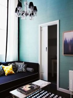 soft turquoise walls, stark white doorframe, black couch, marble top coffee table, dark wooden floor, black and white rug