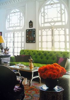 Beautiful green sofa pops against a white backdrop and elaborate window architecture.