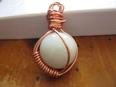 copper wire art - copper wire wrapped around pearl marble pendent.   http://katlynmanson.deviantart.com/art/copper-wire-wrapped-pearl-marble-pendant-313654111