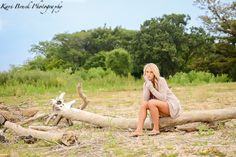 2014 High School Senior girl for posing picture ideas. Senior girl sitting on a beach by the lake on a sandy beach. High school senior session pose inspiration for senior pictures.