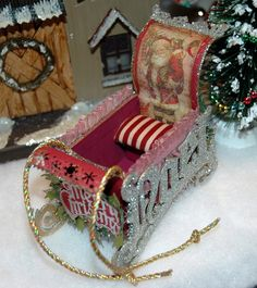 This is a little Santa's sleigh I created out of Tim Holtz' NOEL die cut.  I used the NOEL as the runners for the sleigh.  The rest of sleigh is made out of either chipboard or cardstock.