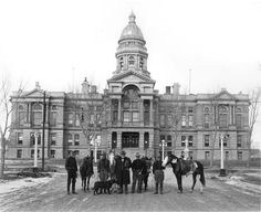 Gov. JM Carey (center holding a small dog) and others with horses in front of the Wyoming State Capitol Building, ca 1914. Photo from the Wyoming State Archives.