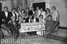 Members of the cast of ITV's soap opera Coronation Street, crowded around a cake replica of the street at the celebration to mark its 25th anniversary at the Dorchester Hotel. Front row, left to right, Julie Goodyear, Eileen Derbyshire, series creater Tony Warren, William Roache, Jean Alexander and Betty Driver. Back row, left to right, Nigel Pivaro, Johnny Briggs, Michael Le Vell, Bill Tarmey, Thelma Barlow, Anne Kirkbride, Bryan Mosley, Lynn Perry, Kevin Kennedy, Bill Waddington,
