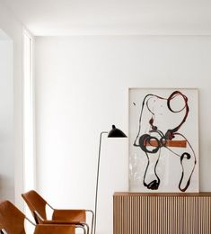 love the statement artwork over the mid century modern credenza