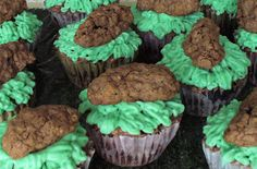 """What doggies doo-doo cupcakes!  A chocolate cupcake with chocolate chips and a chocolate ganache center, smothered under a cream cheese frosting of """"grass"""" and topped with a doggie doo-doo chocolate and cereal cookie!   Made with Camino fair trade cocoa powder."""