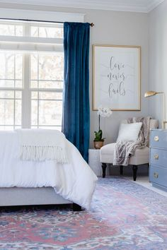Masterbed, closet corner. White chair; blonde tree trunk side table stained darker to match bedroom furniture; SaturdayEveningPost oversized painting. Lamp or potted plant? Probably books.