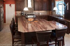 The Deep Purple granite fits in beautifully with the dark, earthy tones of this kitchen. The double tier island provides space for both dining and work.