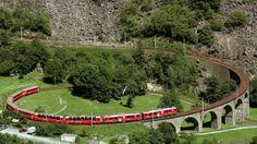 Ein Zug der Rhätischen Bahn (RhB) durchfährt das Kreisviadukt der Berninalinie bei Brusio im Puschlav im Kanton Graubünden.