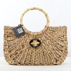 wimberly straw bag with queen bee black enamel embellishment and bamboo handles