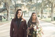 Los angeles halloween inspired wedding shoot at the mountain view cemetery bride black wedding gown with high neckline and lace detail with black sheer veil holding white and dark red floral bridal bouquet with groom burgundy tuxedo with black dress shirt and black faux leather bow tie holding hands