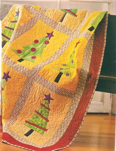 Festival of Trees.  I like the yellow background, unusual in a Christmas quilt.