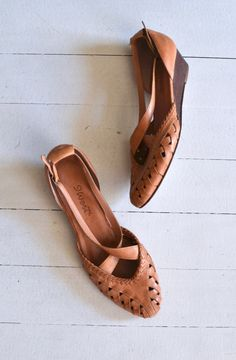 Vintage 1970s, early 1980s tan cutout leather wedges with cross-cross straps, slightly rounded toe, nice leather insole, side buckle and wooden wedge.