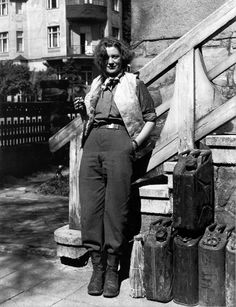 Portrait of Lee Miller with the essentials of life - a cigarette, wine and petrol, 1945 David E. Scherman