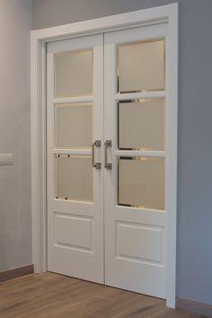 Puerta corredera lacada en blanco. Las puertas tienen cuarterones acristalados con cristales al ácido y bisel, también tienen molduras en bajorelieve y las tapetas son de estilo americano.