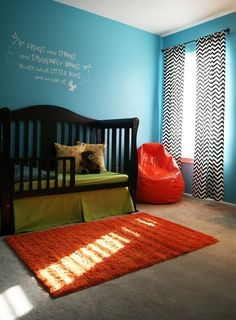 cute color scheme for kids bathroom...blue wals, orange accents, black and white chevron curtain and black cabnet and black trim around mirror