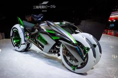 "This Tron-style Kawasaki concept, called the J, is an electric motorcycle where the front ""wheel"" splits into two. The J eschews handlebars ..."