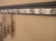Gray jewelry hanger This necklace organizer storage rack has 9 decorative cabinet knobs on gray with white embossed background 26 inches