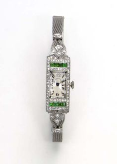 AN ART DECO EMERALD AND DIAMOND WRISTWATCH, BY TIFFANY & CO.   With mechanical movement, the rectangular cream-colored dial, with black Arabic numerals and blued-steel hands, within a circular-cut diamond rectangular bezel, enhanced by rectangular-cut emeralds, to the mesh band, mounted in platinum, circa 1925, 7½ ins. (length adjustable)  Dial signed Tiffany & Co.; movement by Meylan