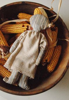A HOMESPUN RAGDOLL, DRIED CORN COBS, AND AN OLD WOOD BOWL.