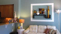 Family Rooms | Interior Creations by Jenifer    By using a shelf with vases at various heights and painting a blue box around the elements it instantly became a cohesive piece of 3-D art that broke up the huge wall behind the sofa.