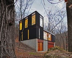 This modest, 880 square-foot cabin for a young family sits at the edge of a small clearing, its compact volume nestled into the densely wooded hillside in a remote Wisconsin forest. The tight budget required a rigorously simple structure. In order