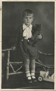 Cute boy hugging teddy bear  and toy car antique studio photo