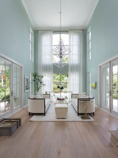 Pale teal walls give a calm vibe to this open living room completed by Margaux Interiors. Spacious Living Room, Formal Living Rooms, Home Living Room, Living Room Designs, Living Room Decor, High Ceiling Living Room Modern, Modern Ceiling, High Ceiling Decorating, Small House Decorating