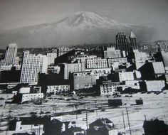 seattle history - - Looking southeast over old downtown Seattle, a snow-covered Mount Rainier