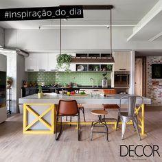 Contemporânea, a cozinha exala charme e graça através da composição com parede em tijolos pintada em tom verde claro. Integrado ao jantar, que traz diferentes modelos de cadeira, o espaço apresenta piso em madeira e mobiliários e revestimentos em uma paleta neutra.
