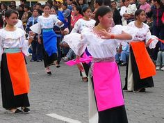 Ecuador's people : This shows an event where the ladies are in different color aprons on a road, kind of like a parade.
