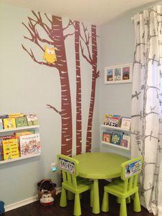 Un rincón de lectura decorado como si estuviese en el bosque